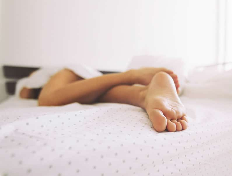 woman feet bed