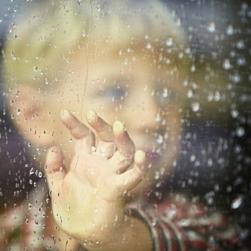 little boy behind the window in the rain - selective focus