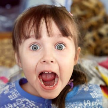 shocked screaming little girl with opened mouth in her bedroom