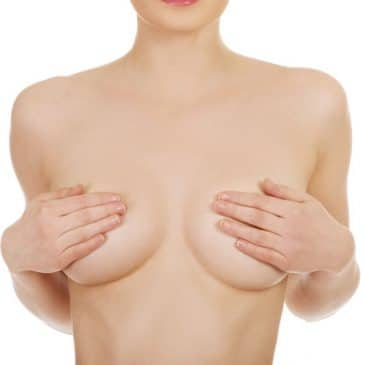 beautiful topless woman covers her breast.
