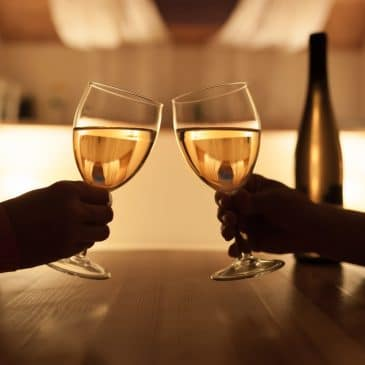 lovers drink wine at table