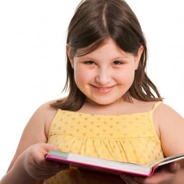 A smiling girl is reading a book; isolated on the white background