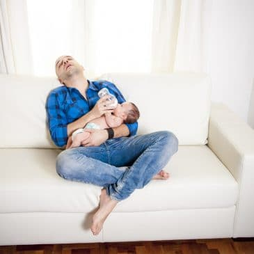 father tired on couch with baby