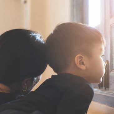 mother and son watching by window