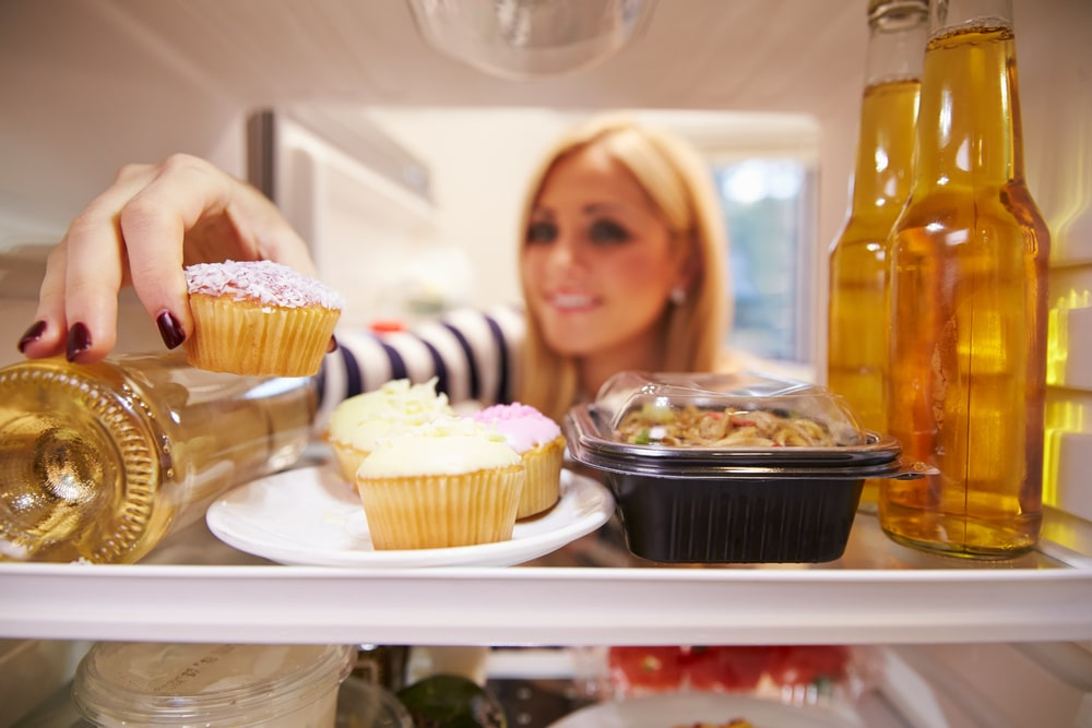 woman fridge with cake and alcohol