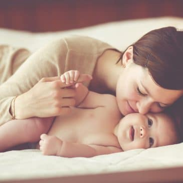 woman kissing baby on bed