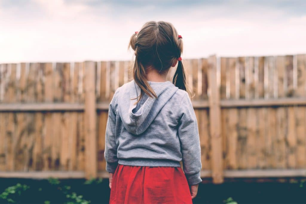 little girl standing in front a fence