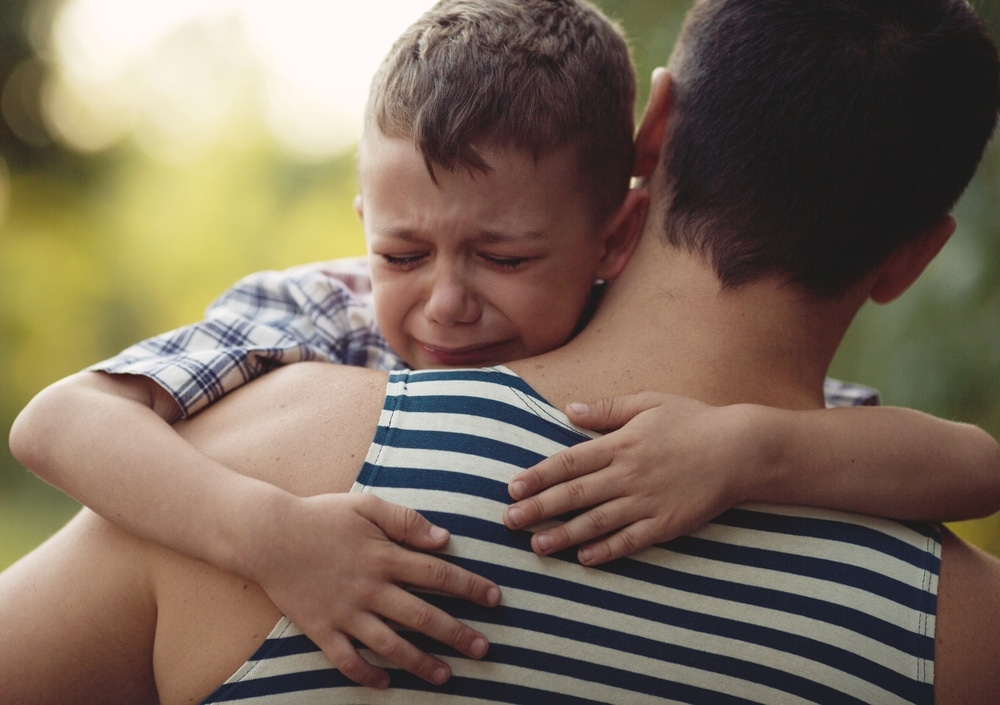 kid crying in man's arms