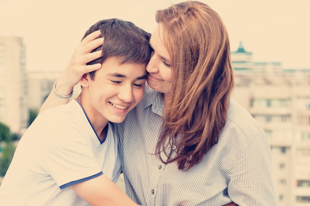 teenager boy and mom hug