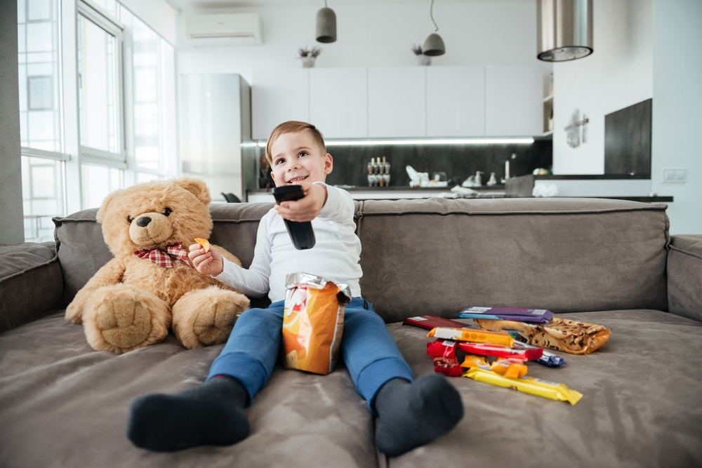 boy watching tv with candies