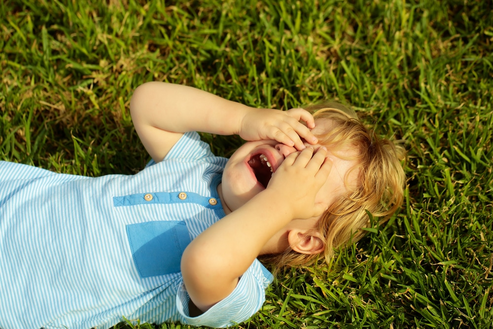 kid crying on grass