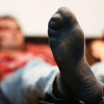 man with foot on couch