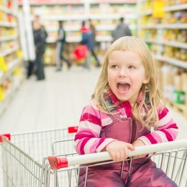 little girl in shopping cart