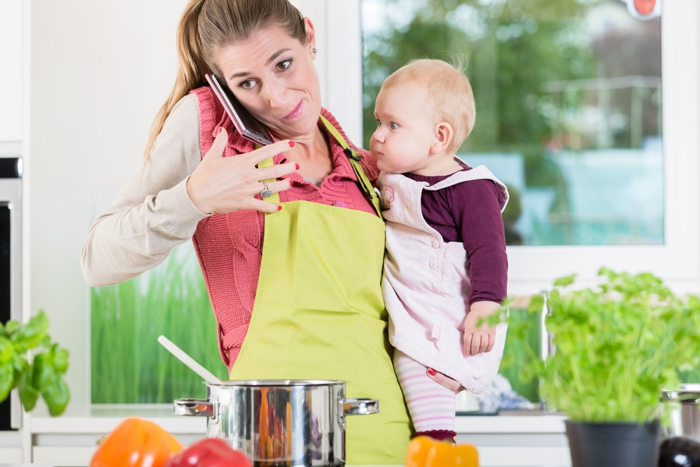 stressed mother cooking with baby and phone