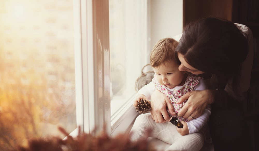 mother and kid in front of window