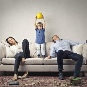 tired parents with kid on couch