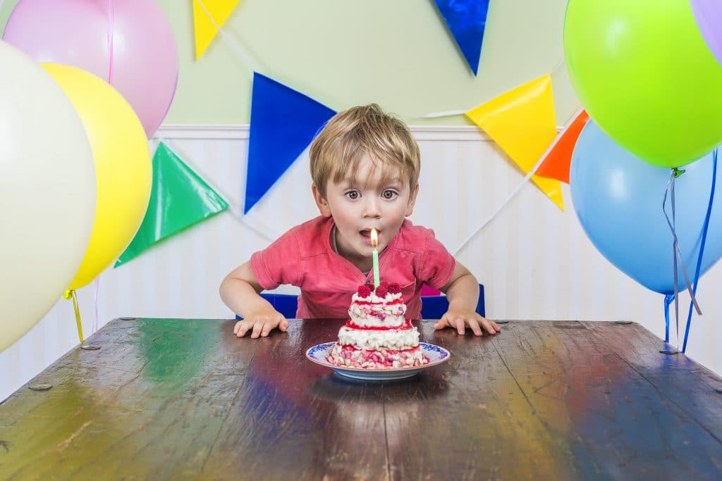 little boy blowing candles on cake