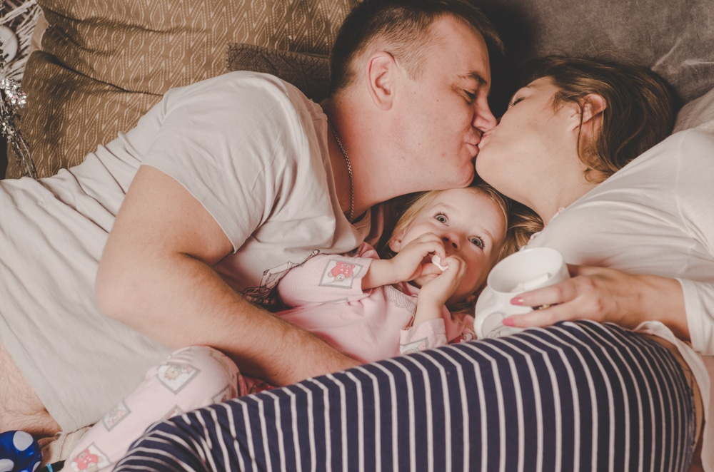 couple kissing in bed with kid