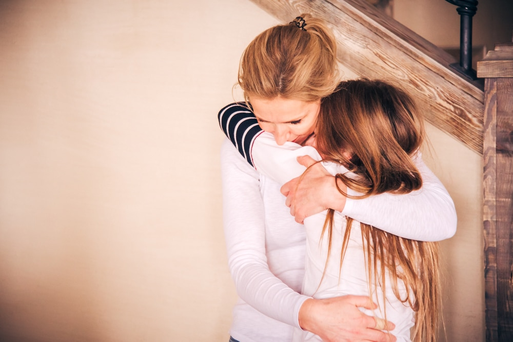 mother embrace crying teenager girl
