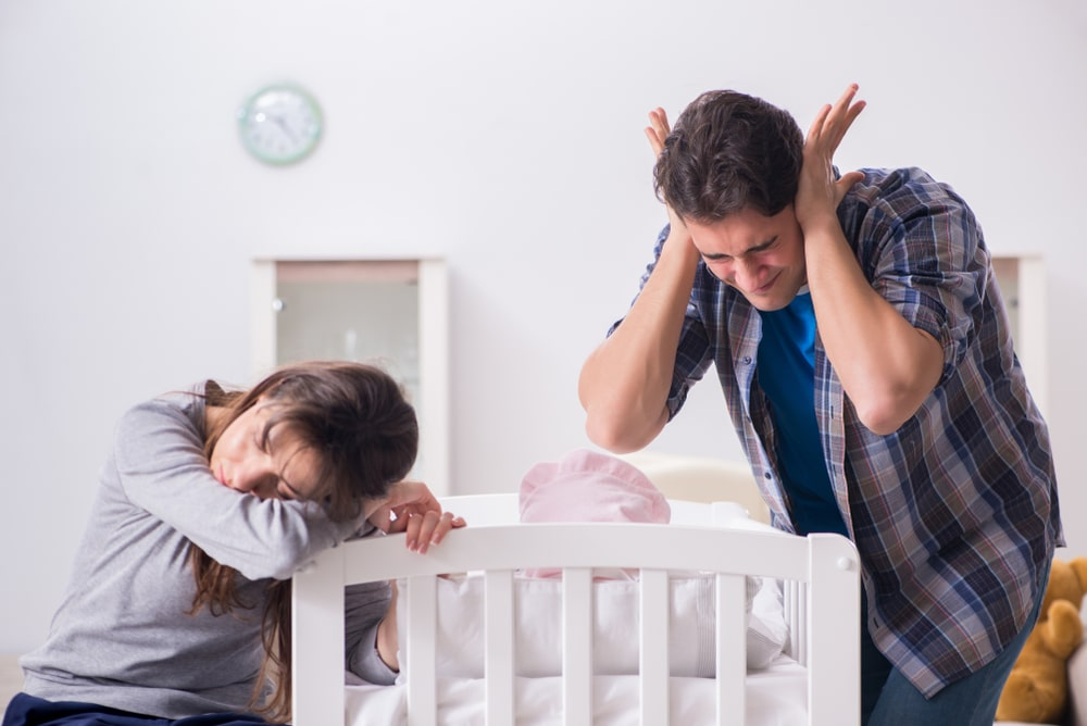 tired mother and father with baby