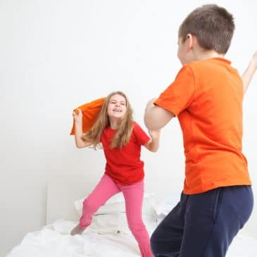 two kids fighting on bed