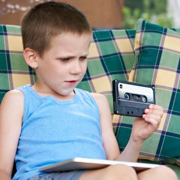 little boy with old cassette
