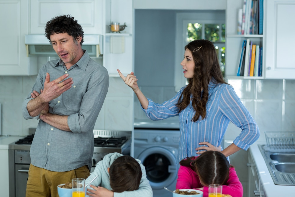 unhappy mother with father and kids in kitchen