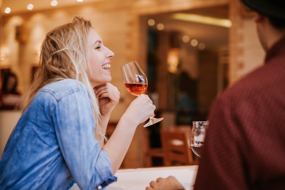 woman laugh with glass of wine
