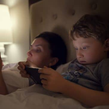 mother and son on bed with cellphone