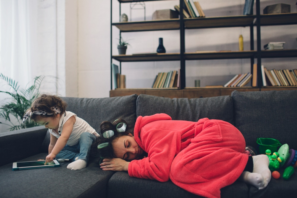 mother sleeping on couch with baby