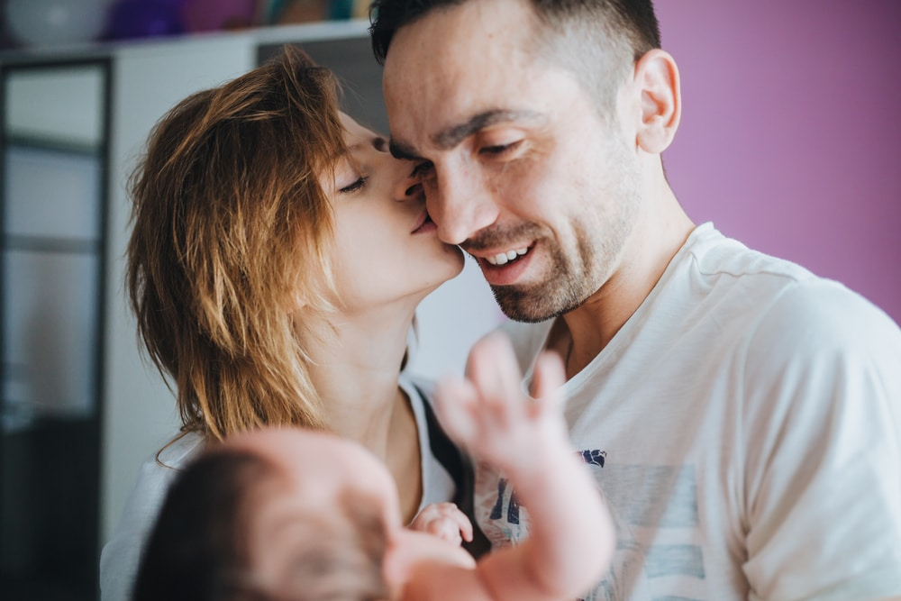 couple kissing with baby