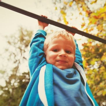 little boy on monkey bars