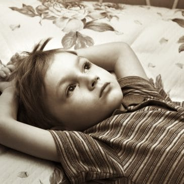 little boy alone on a bed