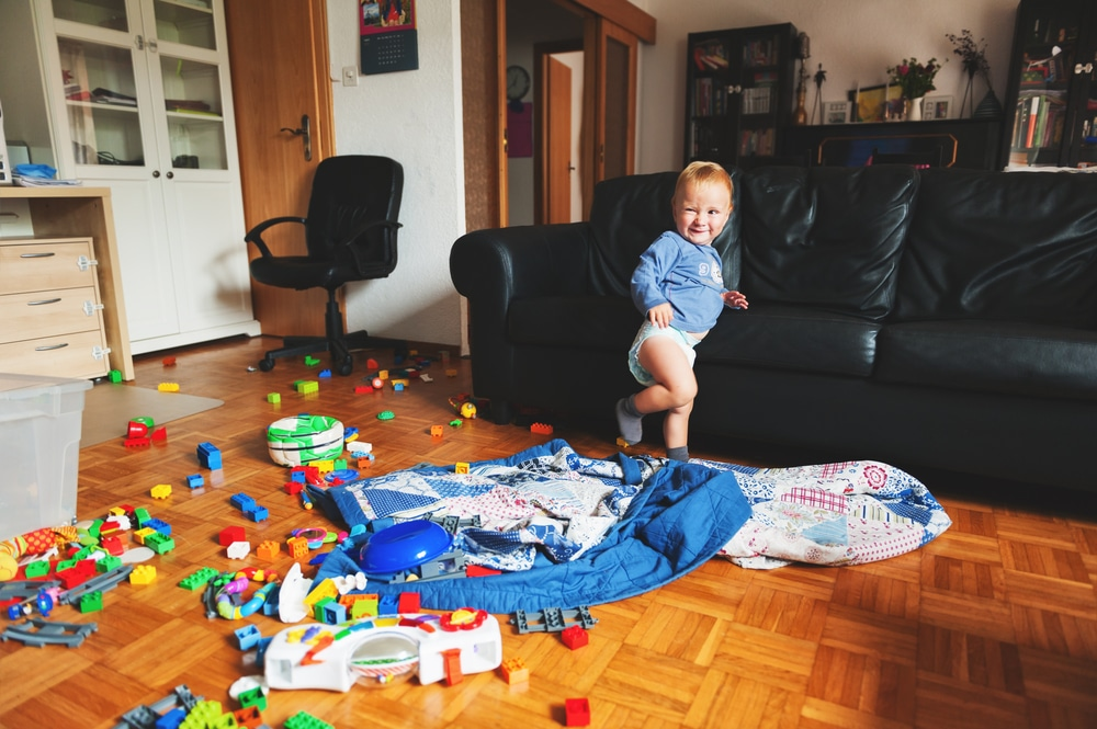 little kid in messy living room