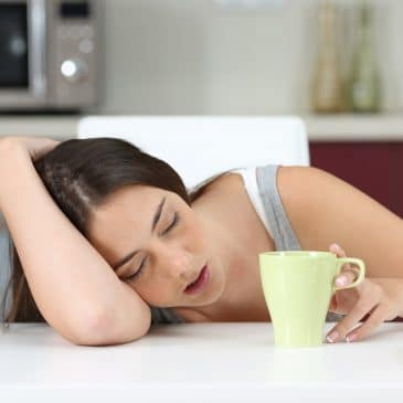 woman tired on table with coffee
