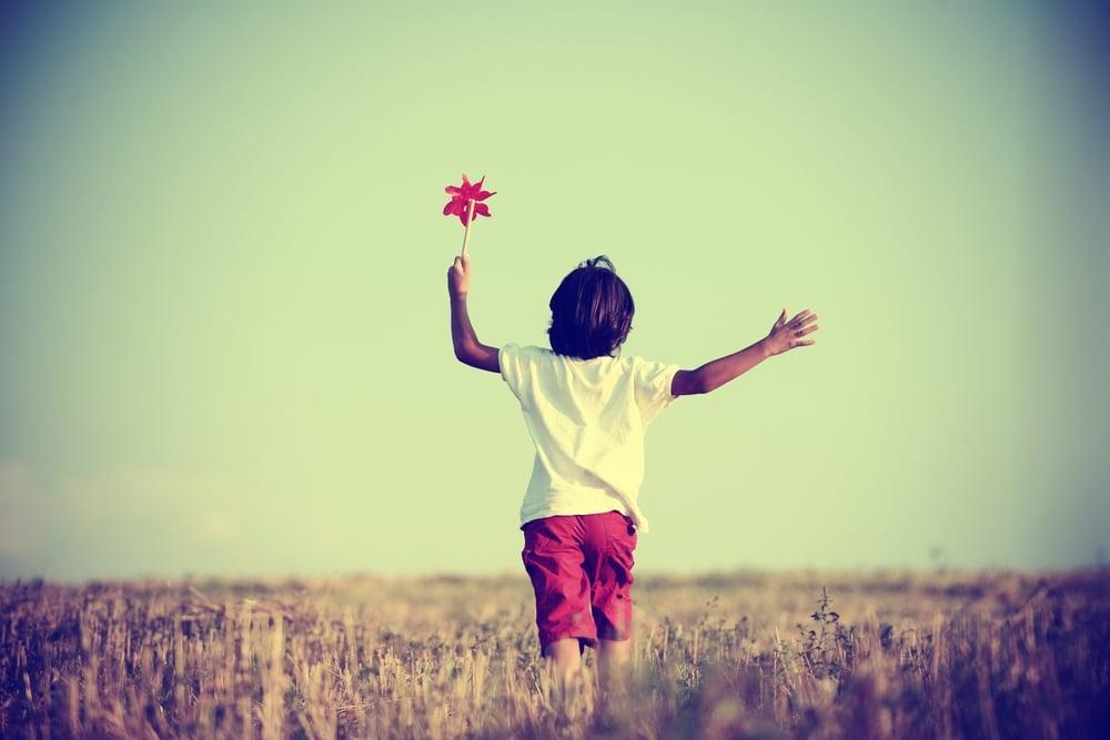 kid walking away in field