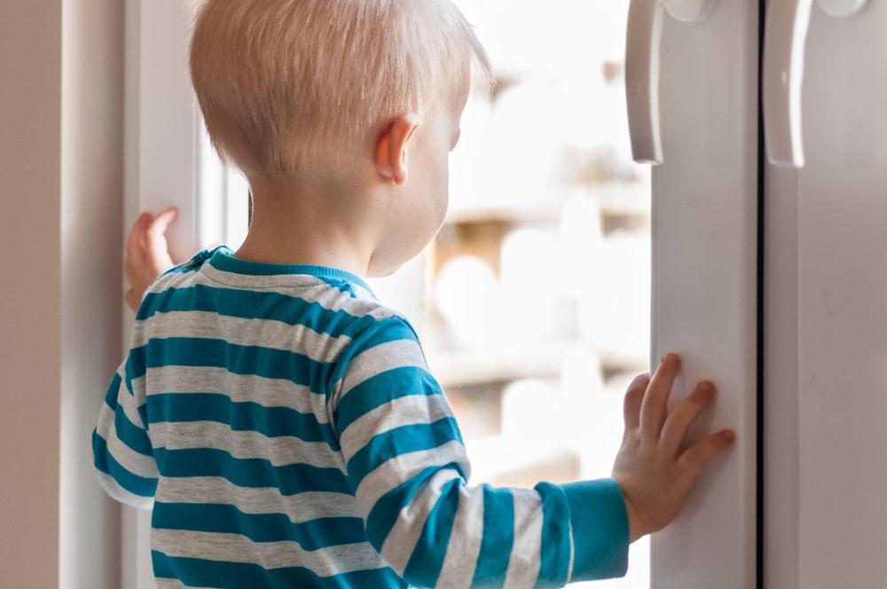 kid behind window