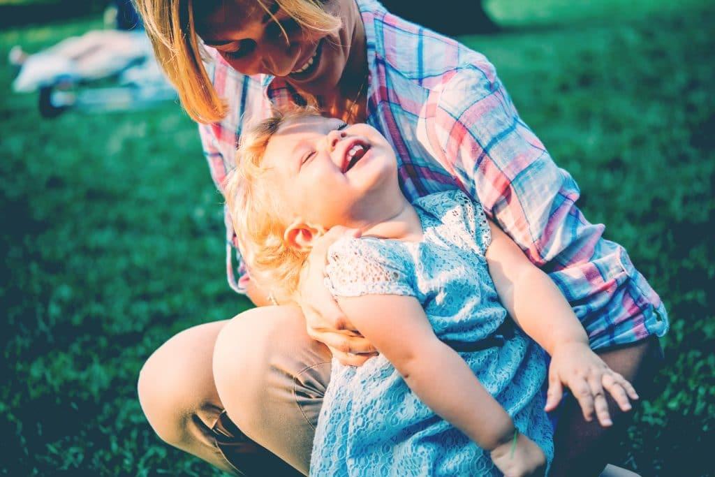 mother and girl hug outside