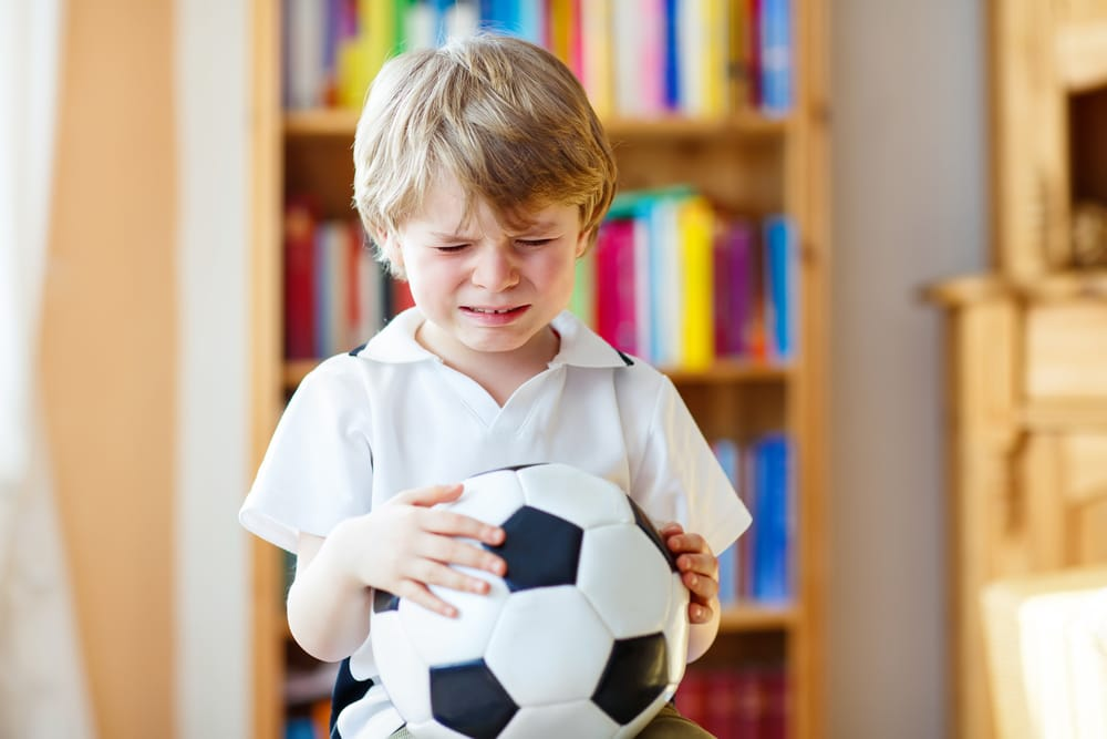 kid crying with ball