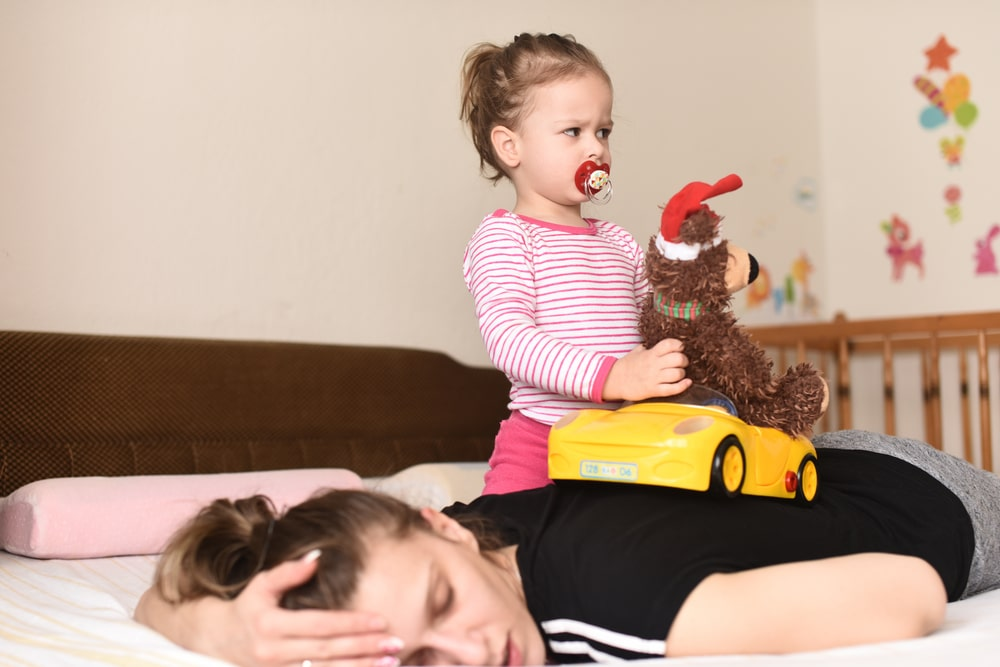 woman trying to sleep with baby