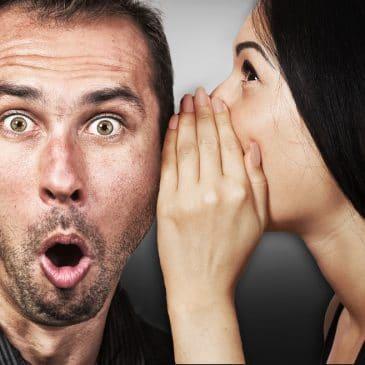 woman telling secret to man
