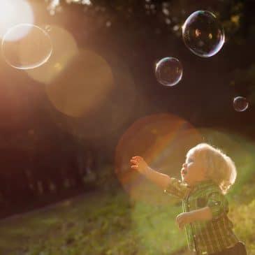 little boy playing outside sunset