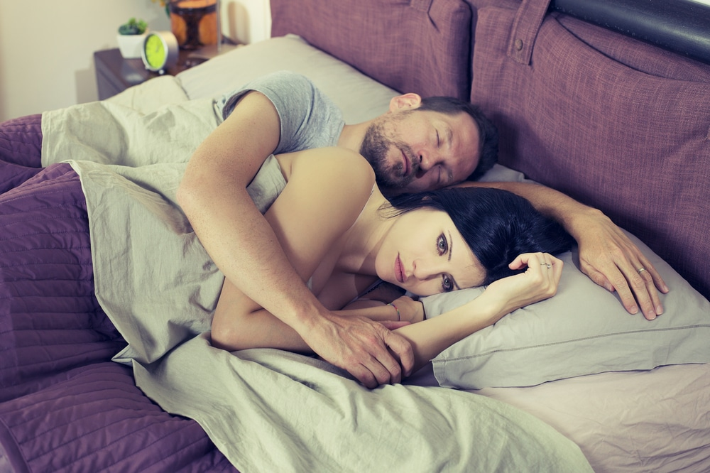unhappy woman with man in bed