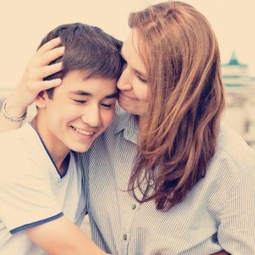 teenager boy and mom hug