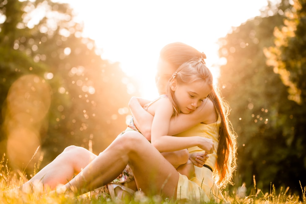 mother and kid embrace sun