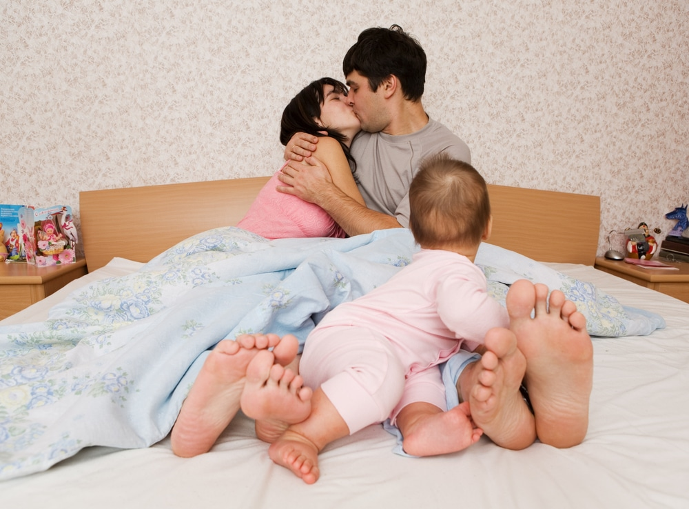 parents kissing in bed with baby