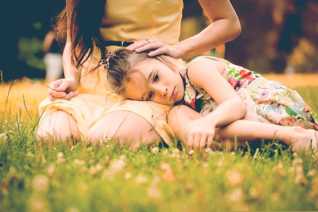 mother embrace little sad girl