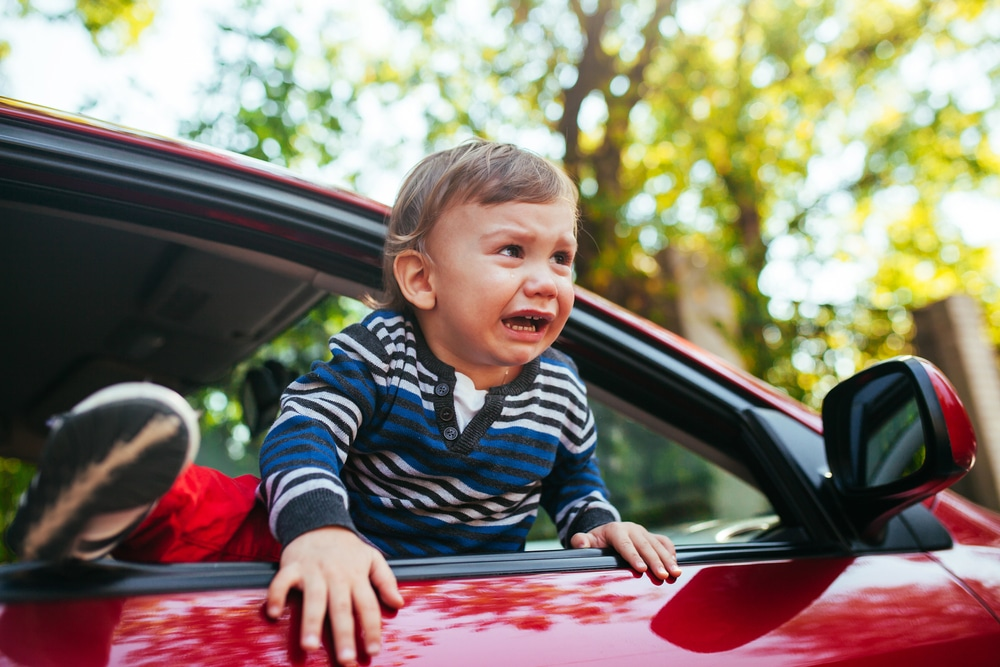 crying baby boy in a car