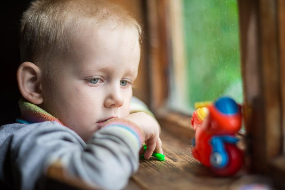little boy in front of window waiting