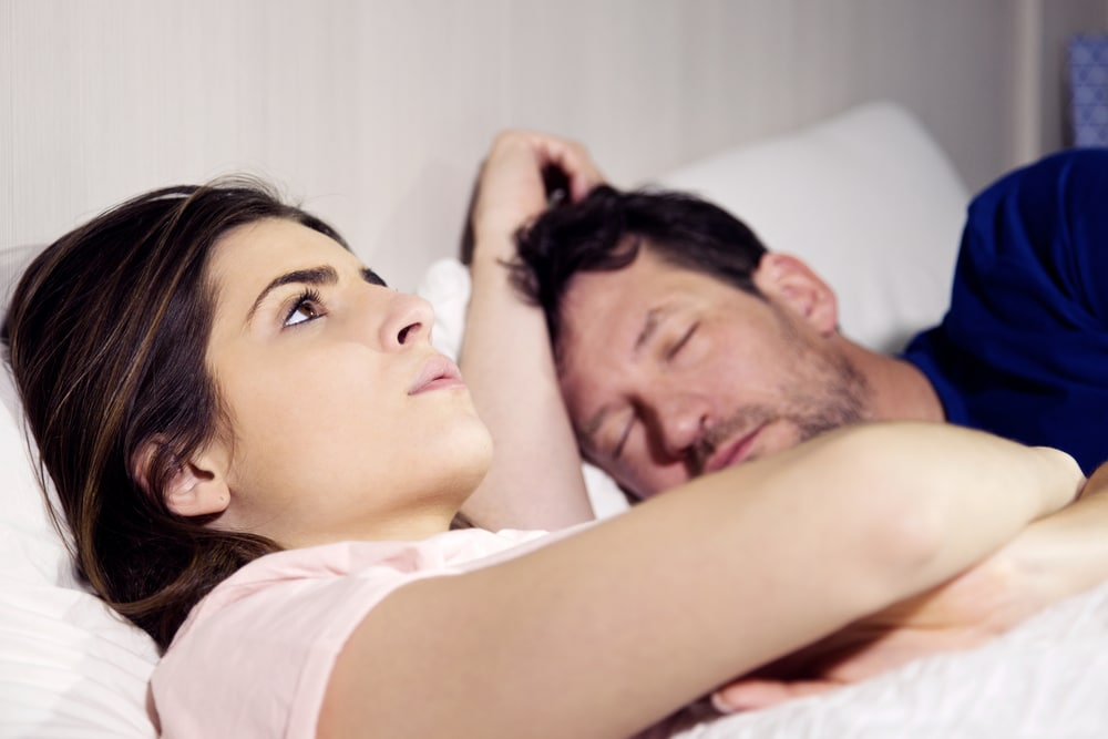 sad woman in bed with husband